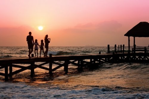 family-standing-on-pier-and-looking-at-sea-at-sunset