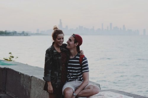 young-couple-sitting-on-ledge-embracing-and-smiling